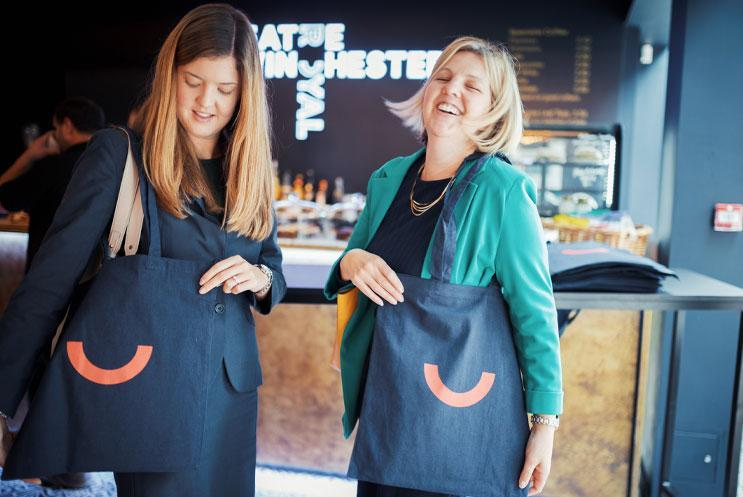 People smiling and holding tote bags