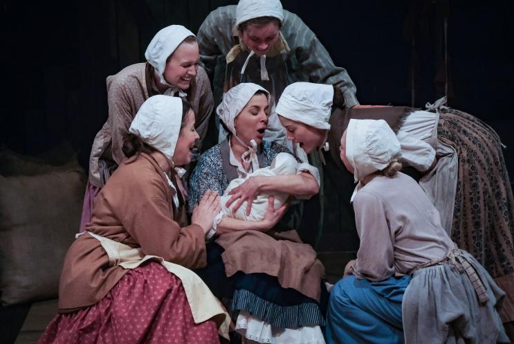 A group of girls huddled around a baby
