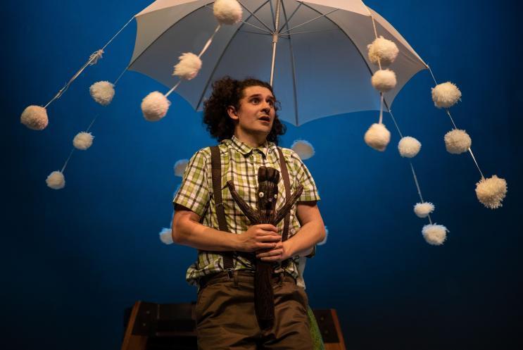 Stick Man and actor under umbrella