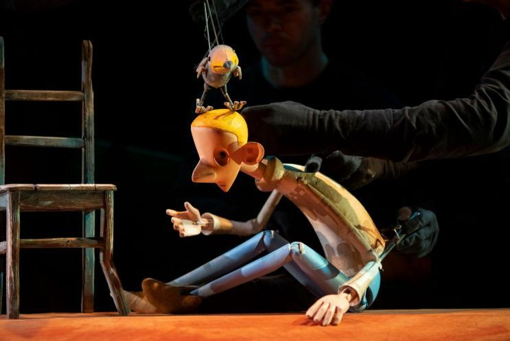 a male puppet and a bird puppet on stage
